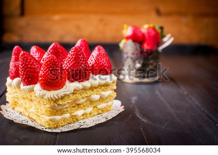 Homemade cream layer cake, fresh, colorful, and delicious dessert with juicy strawberries, sweet whipped cream and cream cheese on a dark wooden background - stock photo