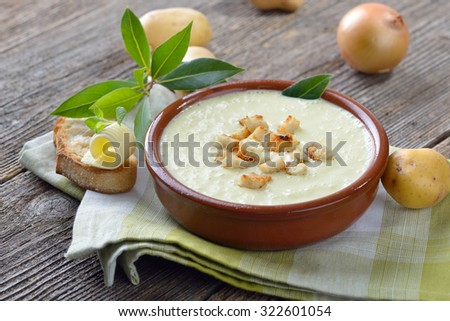 Homemade cream of potato soup  with croutons, served with toasted ciabatta bread with a butter roll - stock photo