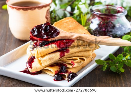 Homemade crepes  folded in triangles with currant jam on spring blossom background - stock photo