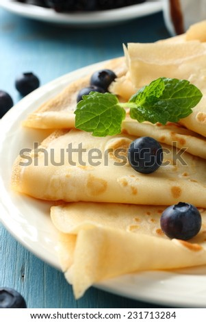 Homemade crepes with blueberries, chocolate sauce and mint - stock photo