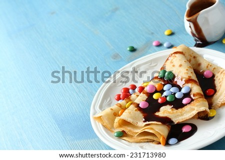 Homemade crepes with multicolored dragee. and chocolate sauce on blue wooden background - stock photo