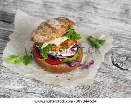 Homemade crispy fish burger on a light rustic wooden board - stock photo