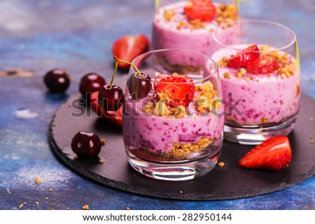 Homemade crubmle dessert with fresh berries and yogurt in glasses on wooden background, selective focus - stock photo