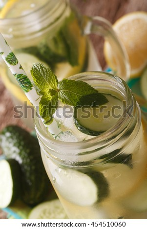 Homemade cucumber lemonade with ice and mint close up in a glass jar on the table. Vertical