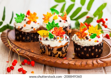 Homemade cupcakes decorated with cream and sugar autumn leaves - stock photo