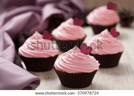 Homemade cupcakes pink traditional Valentines Day sweet dessert with red hearts on vintage cloth background. - stock photo