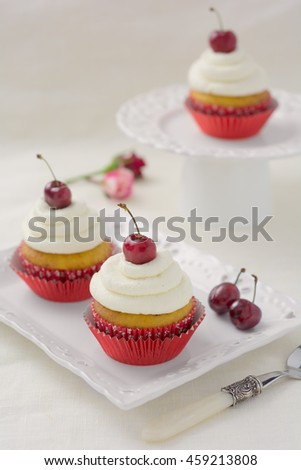 Homemade cupcakes with Chantilly frosting and fresh cherries on-top, presented on white tableware with a vintage spoon and white background.