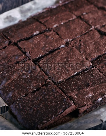 Homemade cut in squares chocolate brownie in backing pan just from oven on dark wooden background - stock photo