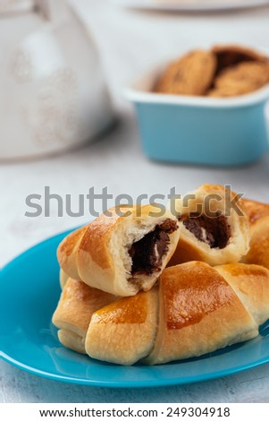 Homemade delicious chocolate croissants on a blue plate. Selective focus.