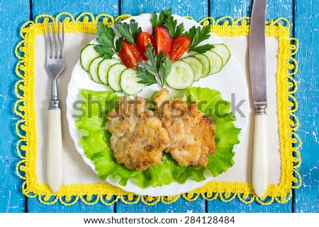 Homemade delicious chopped cutlets with vegetables on a plate, napkin with yellow trim and cutlery on a blue wooden background - stock photo