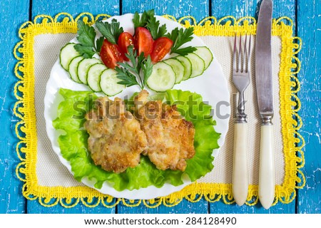 Homemade delicious fried cutlet with vegetables on a plate, napkin with yellow trim and cutlery on a blue wooden background - stock photo