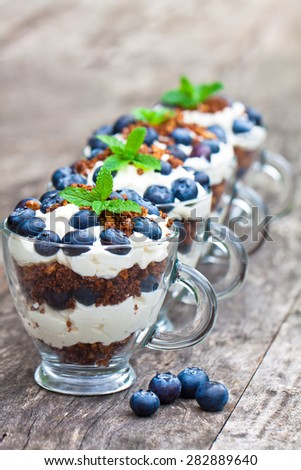 homemade desert with cream chopped cookies and fresh blueberry - stock photo