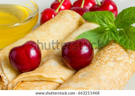 Homemade dessert. Fried pancakes with honey. Crepe with cherry on white plate background. Traditional US meal.