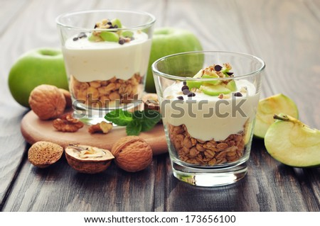 Homemade dessert with apple, nuts, yogurt and granola in glasses - stock photo