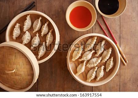 Homemade dim-sum asian dumplings on a traditional bamboo steamer - stock photo