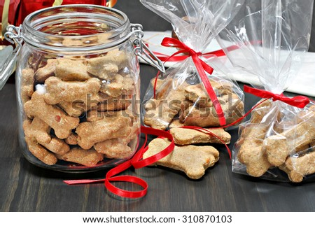 Homemade dog bones being packaged into cellophane bags as healthy gifts for dogs.  Selective focus on foreground cookies.