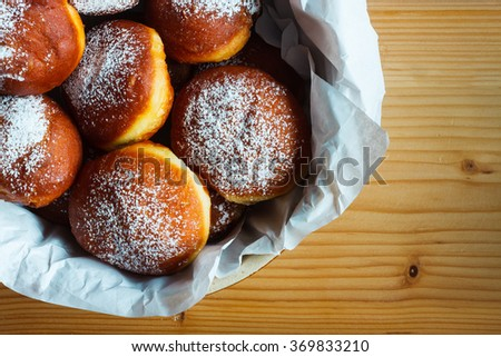 Homemade donuts filled with rose marmalade on wooden table. Rustic style - stock photo
