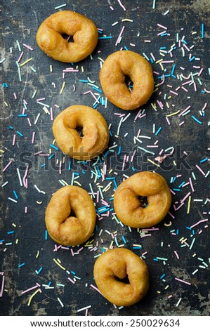 Homemade Donuts over grunge dark background with sprinkled colorful sugar, top view - stock photo