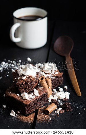Homemade Double Chocolate Cake with Crushed Meringues, Wafer Rolls and Coffee. Dark Wooden Table Background. Moody Atmosphere - stock photo