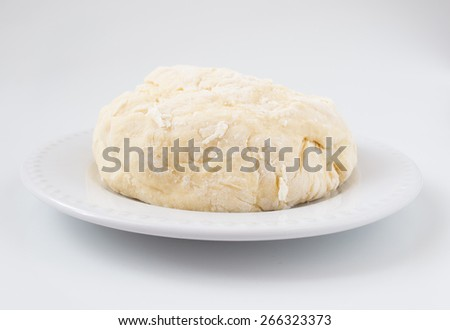 Homemade dough is placed on a flat plate