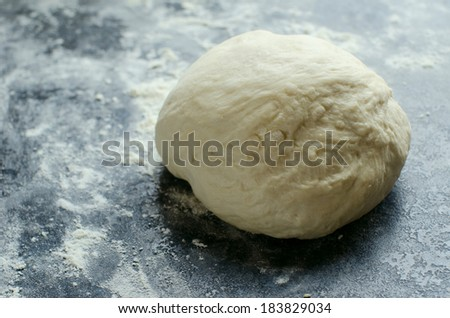 homemade dough laying on wooden plate - stock photo
