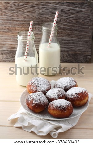 Homemade doughnuts dusted with confectioners sugar, Milk in bottles with paper straws in the background.