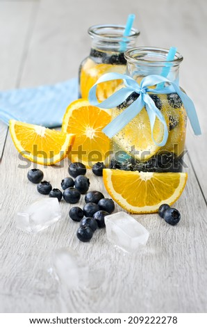 Homemade drink in glasses with straws on wooden surface - stock photo