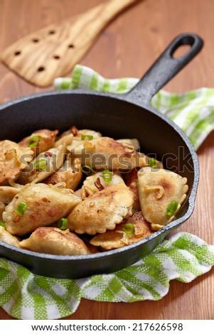 Homemade dumplings fried with onion on a pan - stock photo