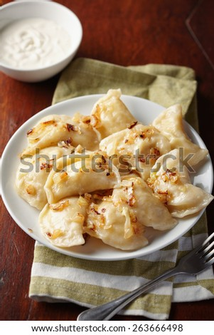 Homemade (dumplings) with potato and onion on a plate.