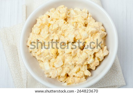 homemade egg salad in white bowl on white background, top view - stock photo