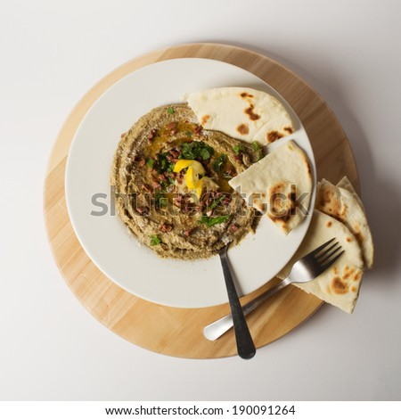 Homemade eggplant hummus, served on a white plate - stock photo
