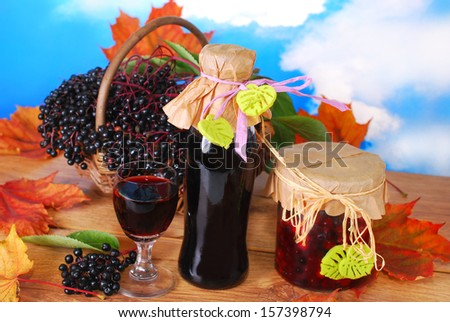 homemade elderberry juice or wine and  preserves with fresh fruits in the basket - stock photo