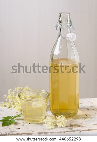 Homemade elderflower syrup in a bottle and glass summer drink with sliced lemon. Selective focus. - stock photo