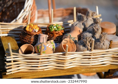 Homemade element of decor: sack, pumpkin, corn, clay jug, dried flowers, amulet,  burlap,  barrel. Clay utensils behind the wicker fence.  - stock photo