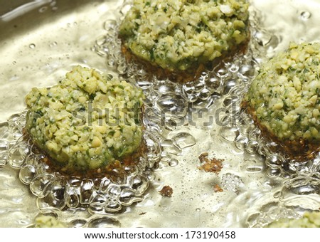 Homemade falafel mixture frying in oil. The balls comprise crushed soaked chickpeas, parsley and coriander leaves, coriander and cumin powder, chilli, paprika, salt and pepper. - stock photo