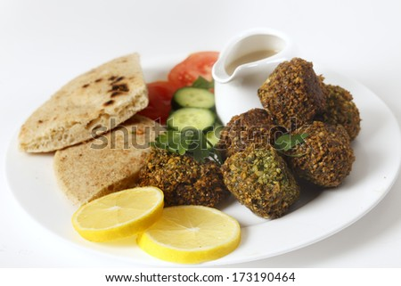 Homemade falafels (herbed and spicy chickpea balls) on a plate with Egyptian flat bread, lemon slices, tomato, cucumber and a tahina sauce. - stock photo