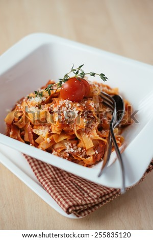 Homemade fettucine pasta with bolognese sauce garnished with cherry tomato, thyme sprig and grated parmesan in a bowl, selective focus - stock photo