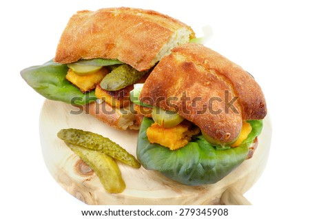 Homemade Fish Burgers with  Fish Sticks, Gherkins, Lettuce, Tartar Sauce and Whole Wheat Bread on Circle Wooden Cutting Board closeup on white background - stock photo