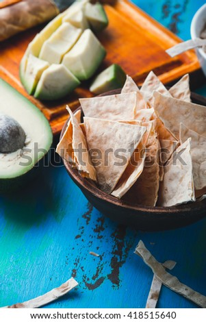 Homemade flour tortilla chips in a ceramic bowl on rustic blue table - stock photo