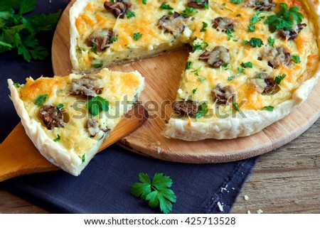 Homemade french quiche pie with mushrooms (champignons) and cheese over rustic wooden background - stock photo