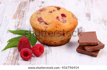 Homemade fresh baked muffins with raspberries and pieces of chocolate on old rustic board, delicious dessert - stock photo