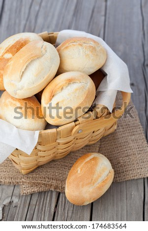 Homemade fresh buns in a basket on old wooden table - stock photo