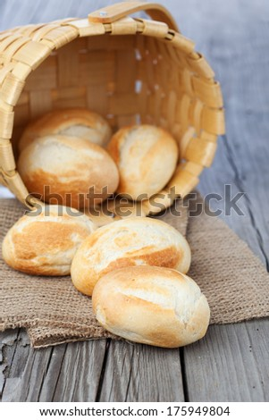 Homemade fresh buns in a basket on old wooden table, selective focus - stock photo