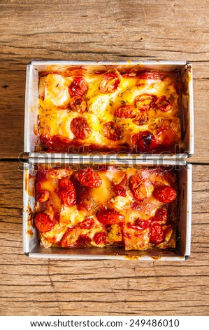Homemade Fresh Lasagna topped with Melted Cheese and Tomato, Oven Baked, Italian Cuisine, On Metal Tin Square Pan / Home Cooking Food Delicious. Top view Close up. - stock photo