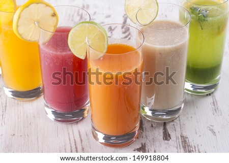 Homemade fresh squeezed couple of colorful juice glasses on a bright wooden background
