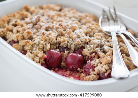 Homemade fresh sweet cherry crumble pie with whole wheat flour on a white kitchen table background ready to eat, closeup