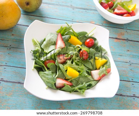 Homemade fresh vegan salad with chopped vegetables, fruits, spring greens and spinach. Arranged on a painted wooden table with side of fruits - stock photo
