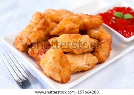 Homemade fried chicken nuggets with ketchup in background  - stock photo