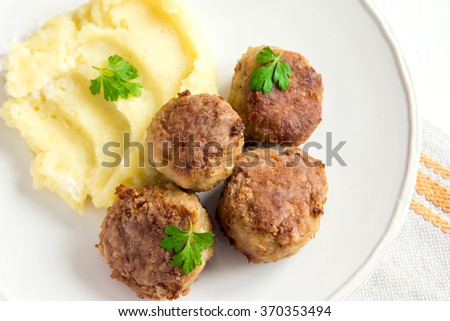 Homemade fried meatballs with mashed potatoes on white plate close up - stock photo