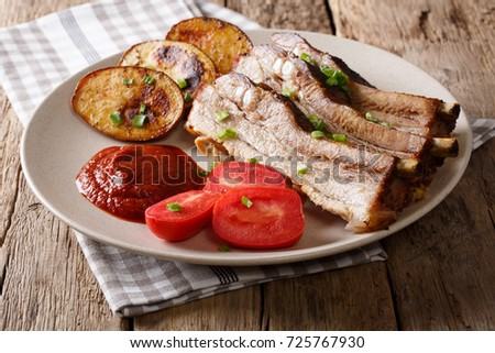 Homemade Fried Pork Ribs with Potatoes on a Plate on a Table. horizontal